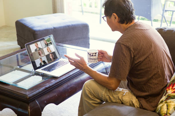 COVID-19 Shelter in Place and Social Distancing in effect, Businessman Working with Virtual Business Group through Live Streaming, video Conferencing Virtual Office stock photo
