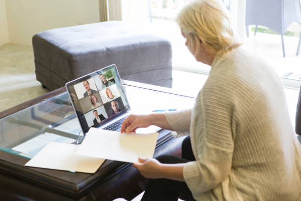 COVID-19 Shelter in Place and Social Distancing in effect, Businesswoman Working with Virtual Business Group through Live Streaming, video Conferencing Virtual Office stock photo