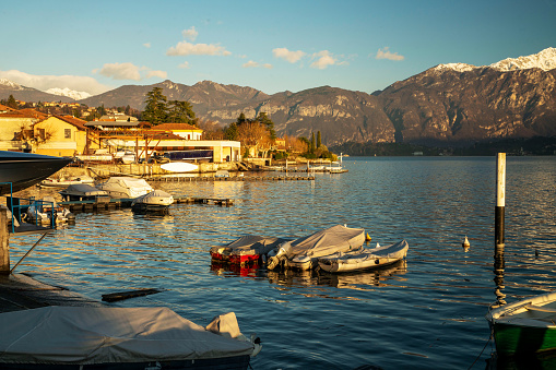 Sheltered boats next to the shore on Lake Como. Sunny day in autumn and winter . sunset coming.