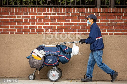 San Francisco, USA - April 4, 2020: San Francisco postal worker in mask delivering mail during stay-at-home order.