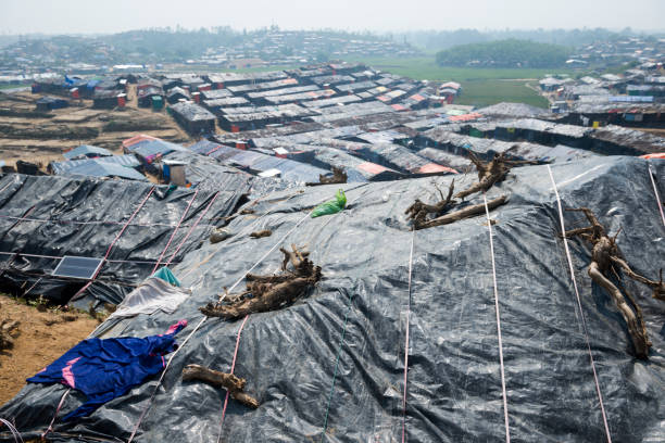 Shelters and landscape at Jamtoli refugee camp in Bangladesh A rural landscape filled with simple shelters at Jamtoli refugee camp, home to tens of thousands of Rohingya Muslims, near Cox's Bazar, Bangladesh. One roof has a solar panel. rohingya culture stock pictures, royalty-free photos & images