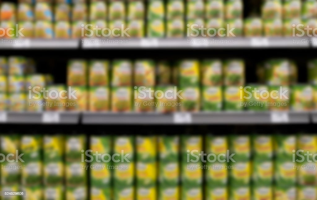 out of focus shelves canned food in supermarket