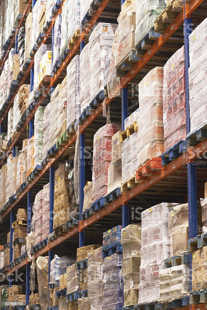 Shelves Full Of Merchandise In Warehouse Low angle view of shelves in warehouse full of merchandise Abundance Stock Photo