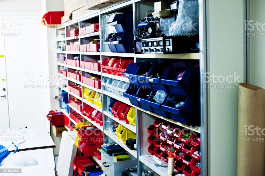 Prateleiras de equipamentos e componentes nas caixas multicor em um laboratório - Foto de stock de Alemanha royalty-free