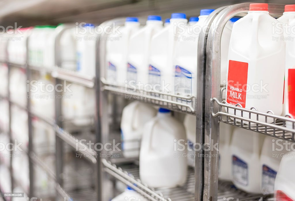 shelves of refrigerated milk in store stock photo