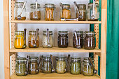 Close up of shelves with a selection of spices and grains in glass jars in zero waste shop