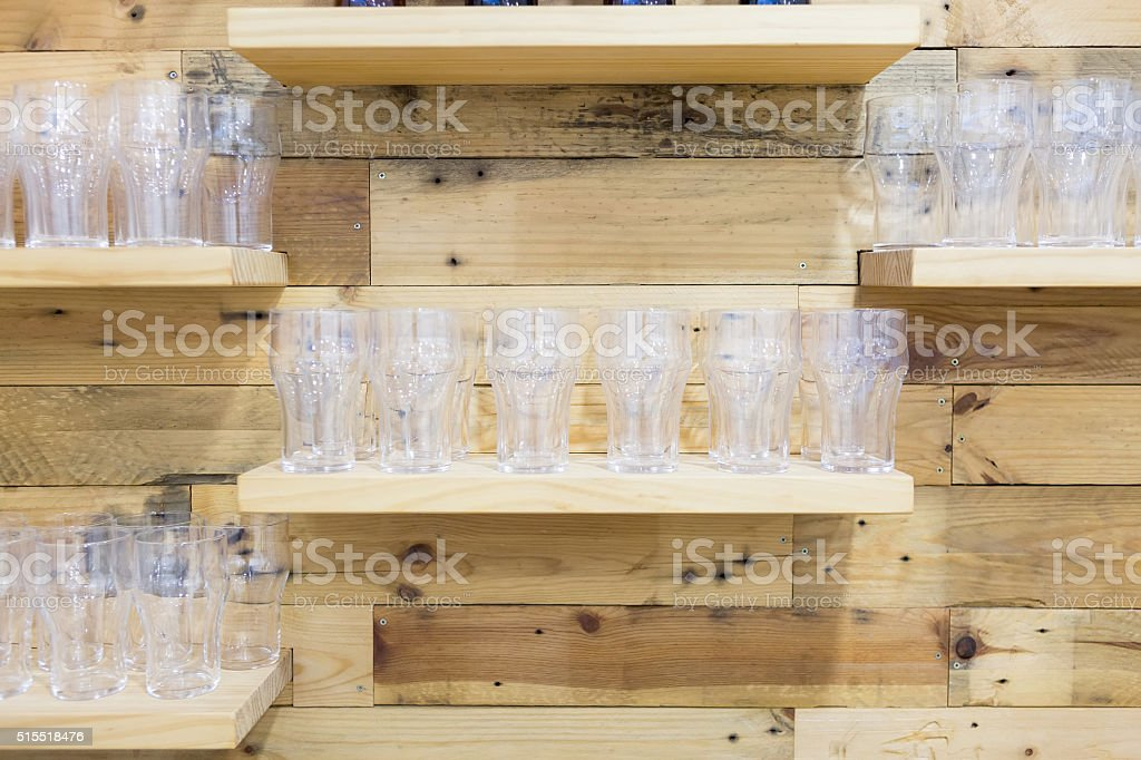 Close-up of wooden shelves with beer glasses standing in a rows
