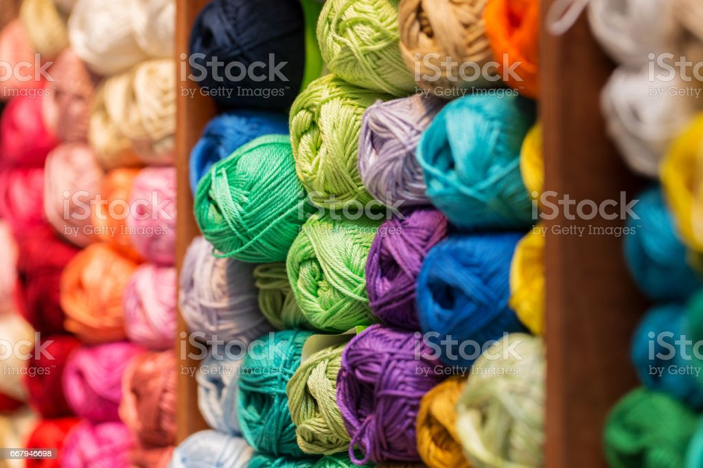 shelves with colorful wool and yarn in a knitting shop stock photo