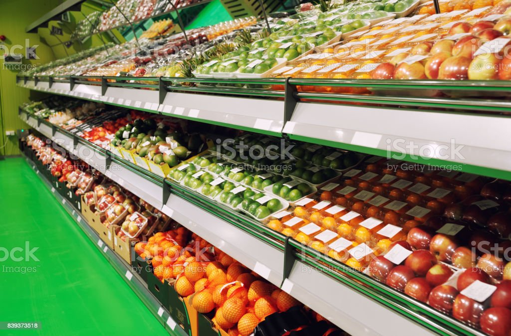 Shelves with fruits in supermarket, toned stock photo