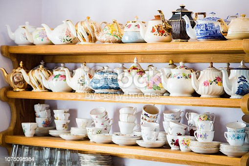 Three shelves with porcelain and ceramics dishes, tea pots and mugs standing by the wall.