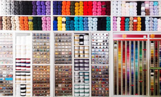shelves with sewing supplies - stoffregal stock-fotos und bilder