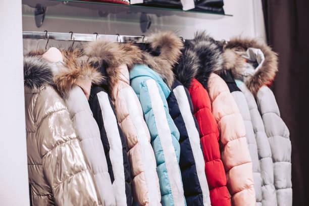 衣料品店で棚。ハンガーに掛かっている天然の毛皮の女性のダウンジャケット。 - ダウンジャケット ストックフォトと画像