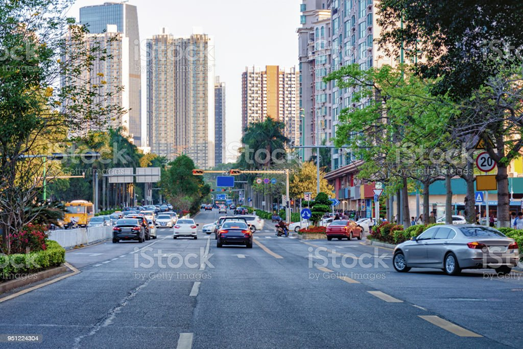 Shenzhen busy city street with moving car, motorcycle, office...