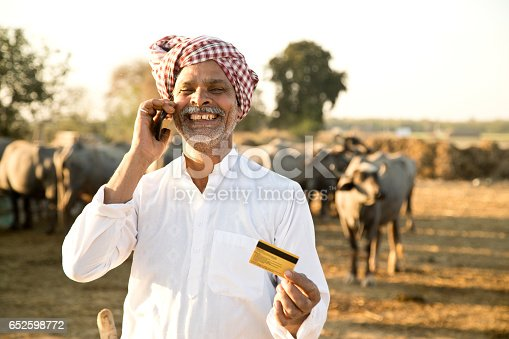 Happy buffalo shepherd using credit card and mobile phone for online payment