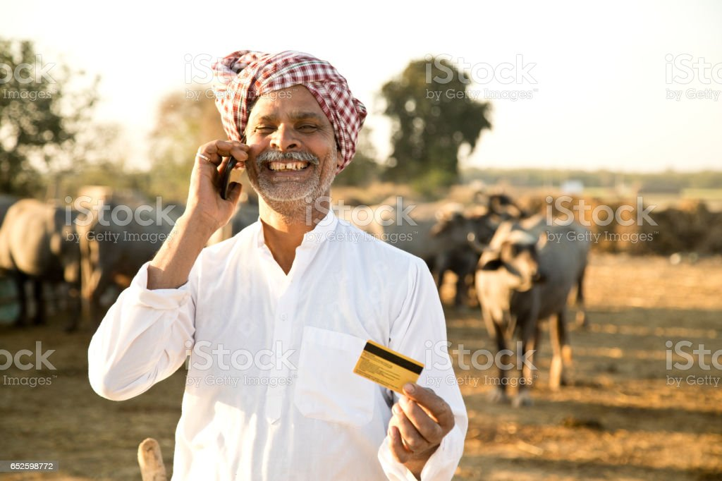 Shepherd using credit card and mobile phone stock photo