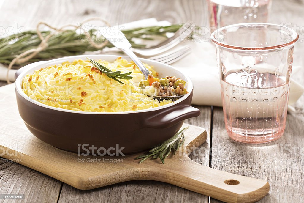 Shepherd's pie in a brown dish on a dining table stock photo