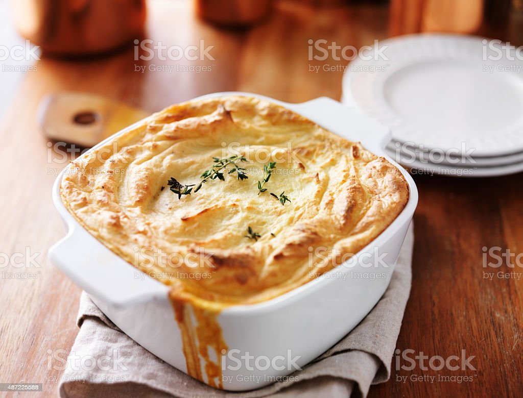 shepherds pie in baking dish on wooden table stock photo