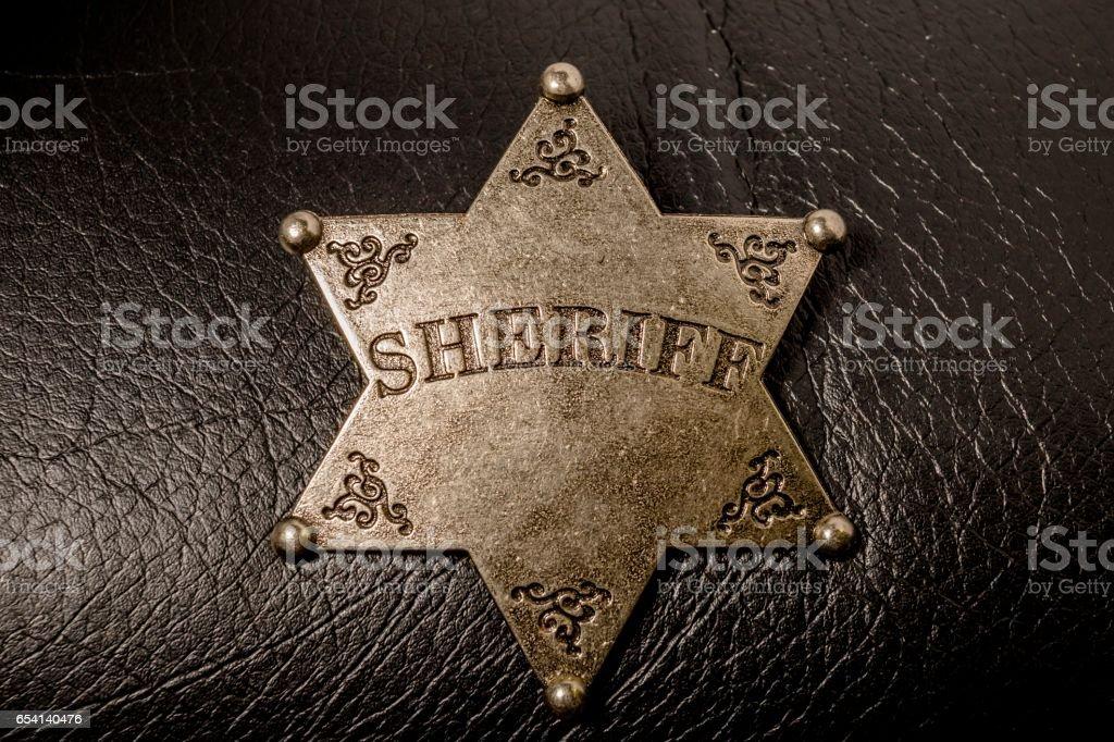 Sheriff badge on black leather texture background. stock photo
