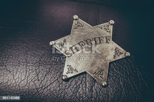 istock Sheriff badge on black leather texture background. 654140486