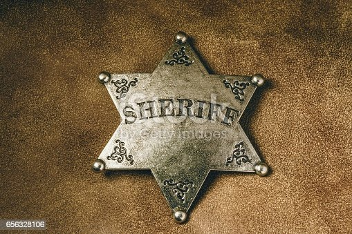 istock Sheriff badge on brown leather texture background. 656328106