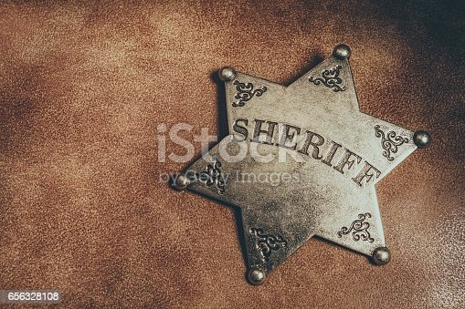 istock Sheriff badge on brown leather texture background. 656328108