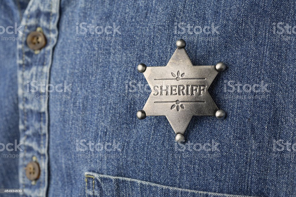Sheriff's badge on a faded denim shirt stock photo