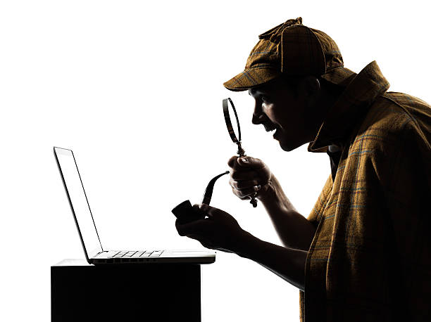 Sherlock Holmes using a laptop sherlock holmes silhouette in studio on white background sherlock holmes stock pictures, royalty-free photos & images
