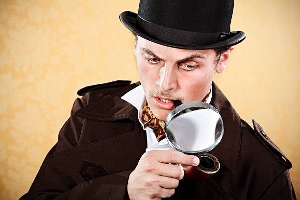 sherlock holmes with hat, trenchcoat, and magnifying glass - sherlock holmes stock photos and pictures