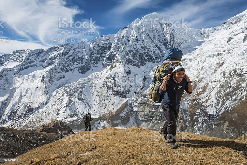 Sherpa guide carrying expedition kit Himalayas Nepal stock photo