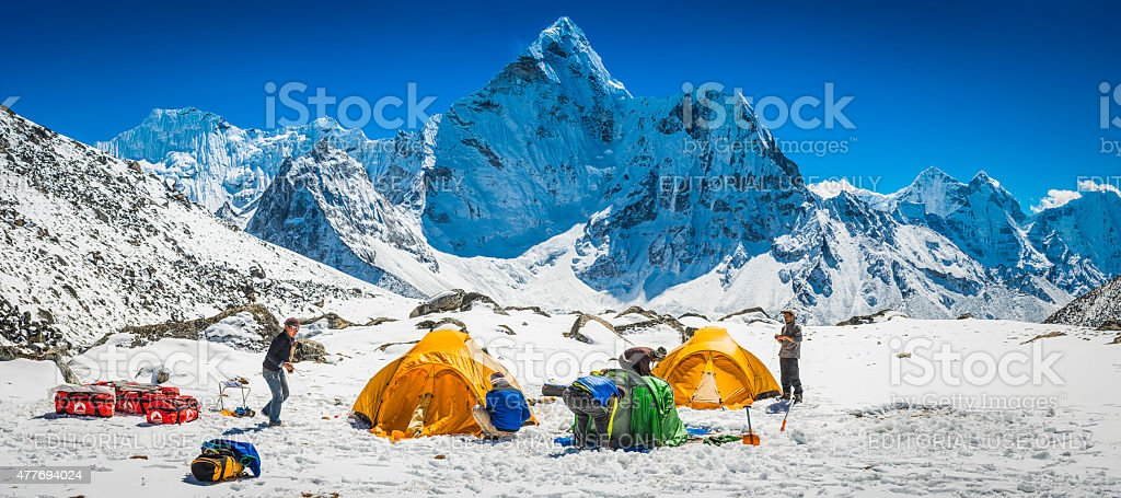 Sherpa mountaineers pitching tents snowy high mountain camp Himalayas Nepal stock photo