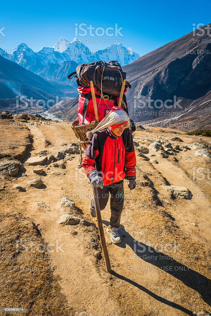Sherpa porter carrying doko bamboo basket Himalaya mountain trail Nepal stock photo