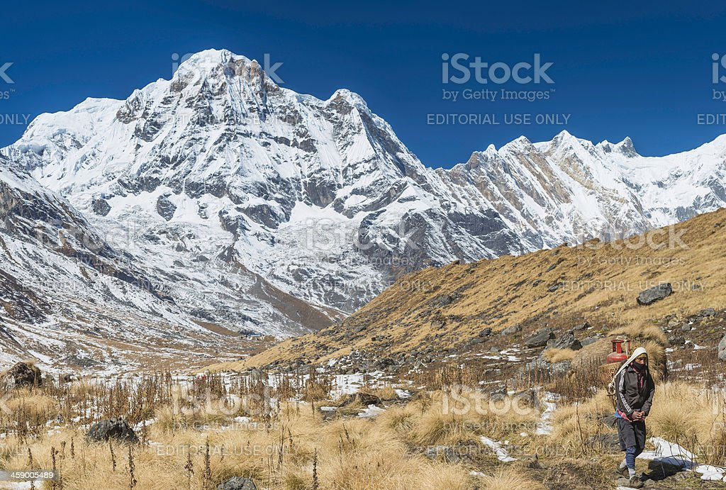 Sherpa porter carrying expedition basket under Annapurna Himalayas Nepal royalty-free stock photo