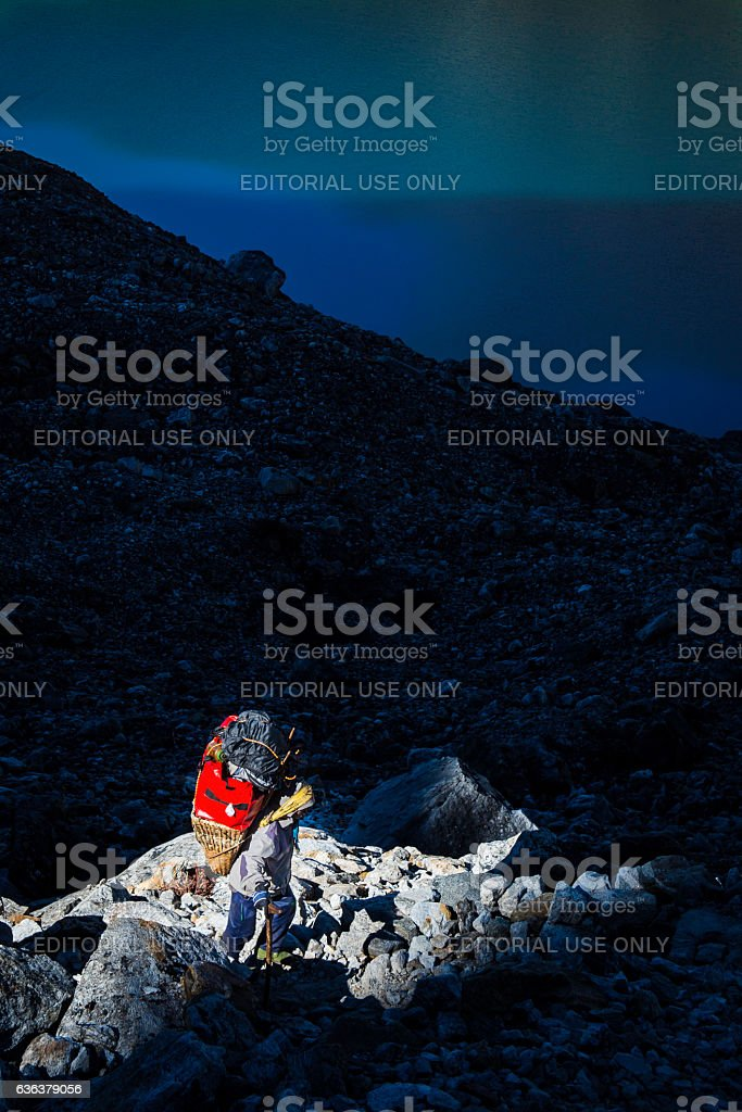 Sherpa porter carrying expedition equipment bamboo basket Himalaya mountains Nepal stock photo