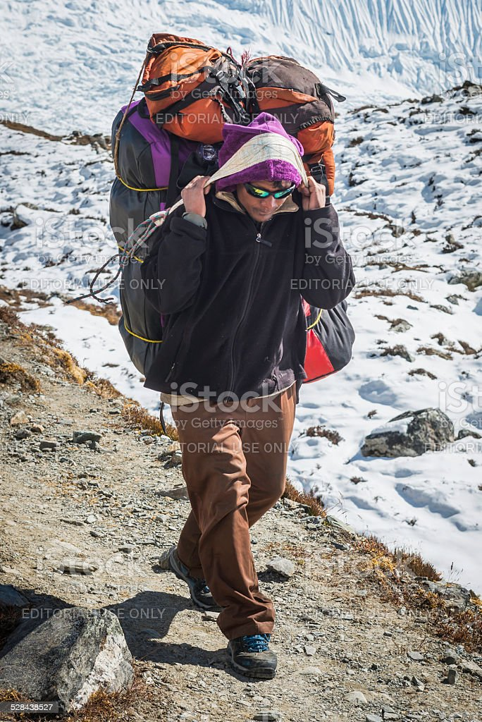 Sherpa porter carrying expedition equipment using headband Himalaya mountains Nepal stock photo