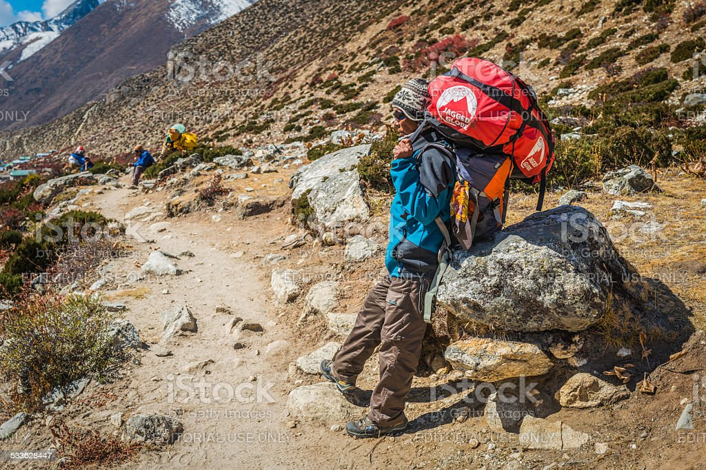 Sherpa porter carrying expedition kit on Himalaya mountain trail Nepal stock photo