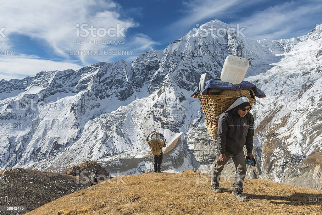 Sherpa porter carrying expedition load high in Himalaya mountains Nepal stock photo