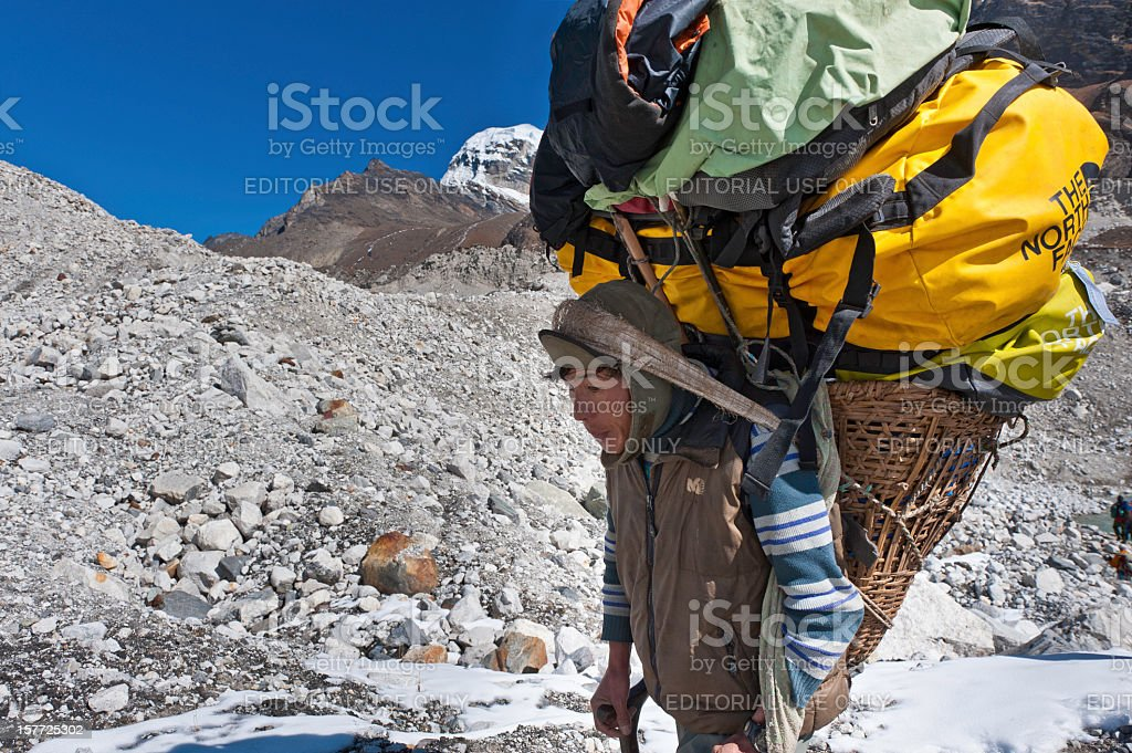 Sherpa porter carrying heavy expedition load across glacier Himalayas Nepal stock photo