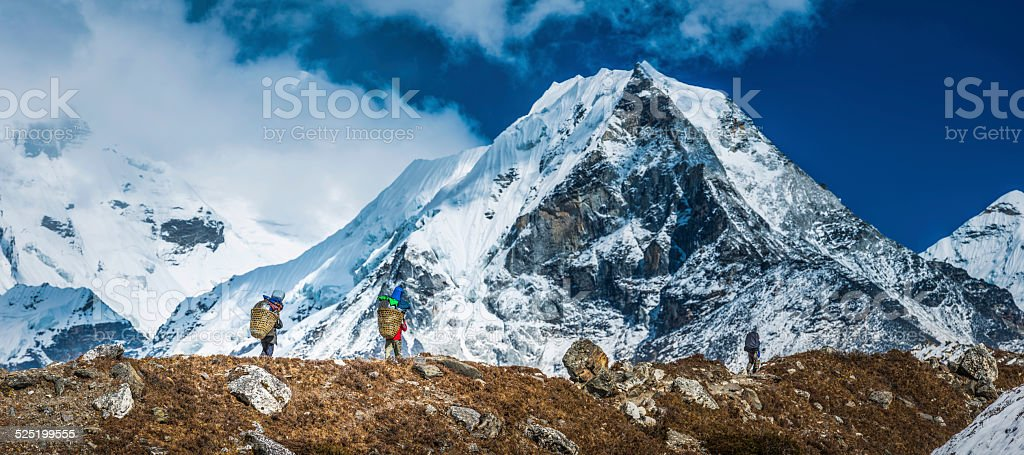Sherpa porters carrying baskets towards Island Peak Himalaya mountains Nepal stock photo