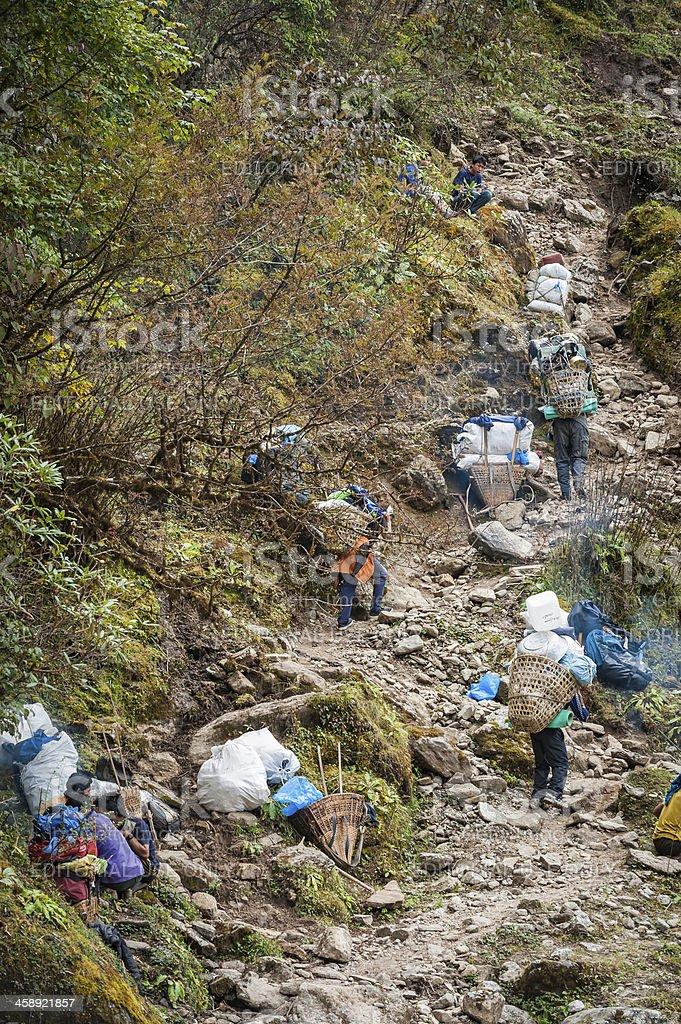 Sherpa porters carrying heavy loads Himalayas Nepal stock photo