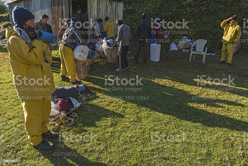 Sherpas and Nepalese porters breaking camp in Himalayas Nepal royalty-free stock photo