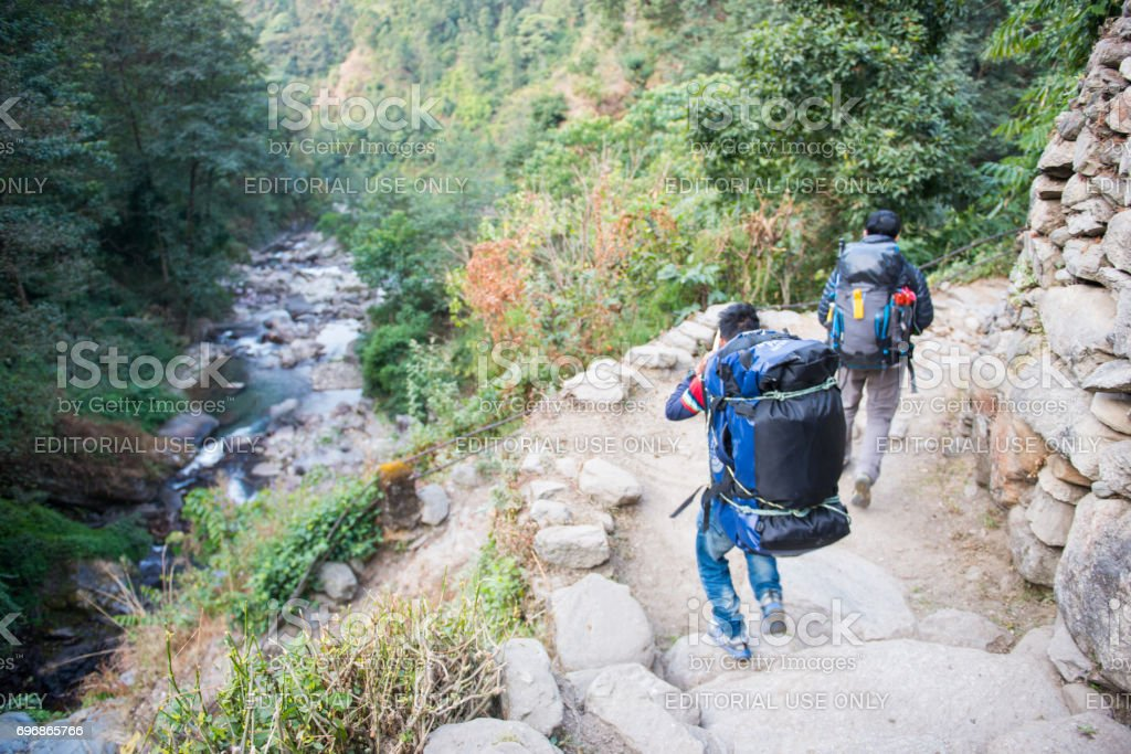 Sherpas carry heavy backpack and walk to mountain stock photo