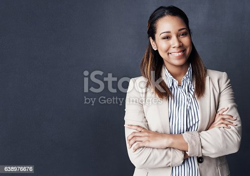Studio shot of a young woman posing against a gray background
