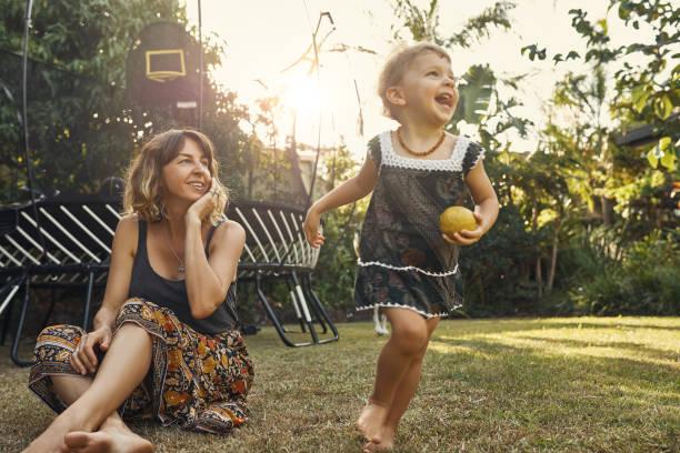 she's a free spirit - mãe criança brincar relva efeito de refração de luz imagens e fotografias de stock