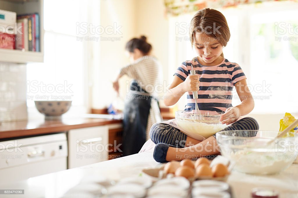 She's a great little helper in the kitchen stock photo