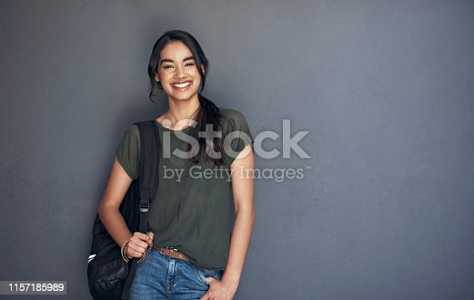 Studio portrait of a young woman carrying a schoolbag against a grey background