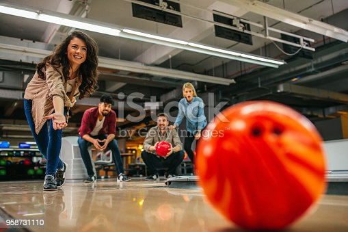 Shot of an attractive brunette throwing the bowling ball