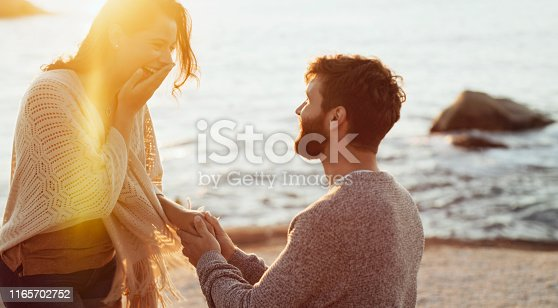 Cropped shot of a young man proposing to his girlfriend on the beach