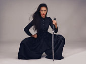 Studio portrait of a beautiful young woman in a martial arts outfit wielding a samurai sword