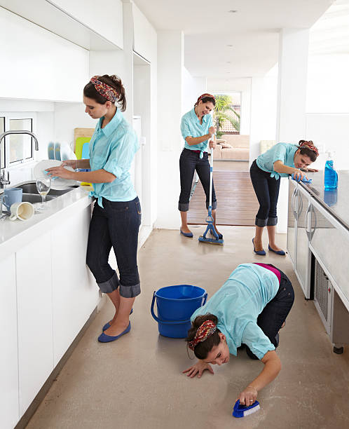She's a whizz at multi-tasking! Multiple clones of one young woman cleaning a kitchen samenwerking stock pictures, royalty-free photos & images