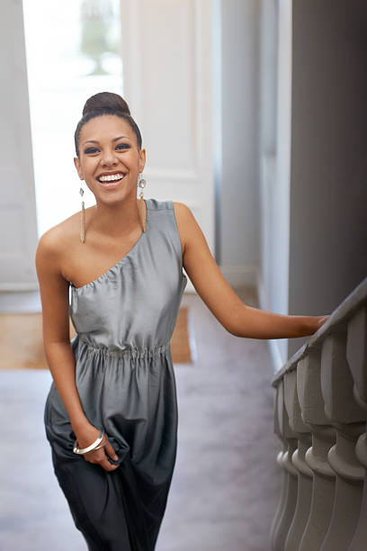 She's all elegance Portrait of an attractive young woman smiling while standing on a staircase evening wear stock pictures, royalty-free photos & images